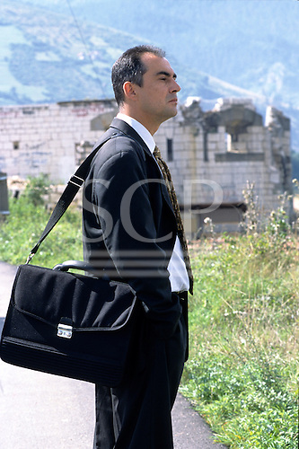 Sarajevo, Bosnia and Herzegovina. Businessman in suit with a black bag looking into the distance; destroyed building.