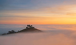 Small island is surrounded by a sea of fog in Dorset, UK by Mark Andreas Jones