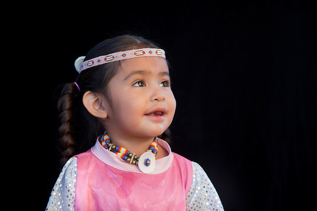 Smiling 2 year old Lillia Baker (Shoshone-Bannock) dressed in beaded headband and choker with braids on black background