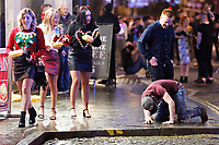 A man falls on the pavement in Wind Street, Swansea, Wales  on Mad Friday, Booze Black Friday or Black Eye Friday, the last Friday night before Christmas Day, when traditionally people in the UK go out to celebrate the start of their holidays. Friday 22 December 2017