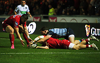 Steffan Evans of the Scarlets passes the ball to team mate Scott Williams (L) while being tackled by Alex Cuthbert of Cardiff Blues during the Guinness PRO14 match between Scarlets and Cardiff Blues at Parc Y Scarlets Stadium, Llanelli, Wales, UK. Saturday 28 October 2017