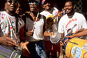 Salvador, Brazil. Smiling musicians playing atabaque and other instruments on the street.