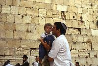 ISRAELE, Gerusalemme. Un ebreo con la kippah abbraccia il suo bambino al Muro del pianto.