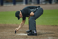 Home plate umpire Lane Cullipher brushes off home plate during the game between the Down East Wood Ducks and the Kannapolis Cannon Ballers at Atrium Health Ballpark on May 8, 2021 in Kannapolis, North Carolina. (Brian Westerholt/Four Seam Images)