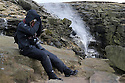 01/02/14<br /> <br /> A photographer protects himself against 45 mph winds and a wind-chill adjusted temperature [measured] of minus ten as the Kinder Downfall waterfall blows up the rocks back on to the Kinder Plateau high up in the Derbyshire Peak District.  <br /> <br /> F Stop Press.  www.fstoppress.com. Tel: +44 (0)1335 300098