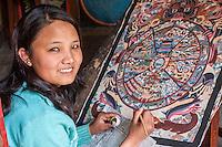 Nepal, Patan.  Young Woman Painting a Thangka, a Tibetan Buddhist Painting.