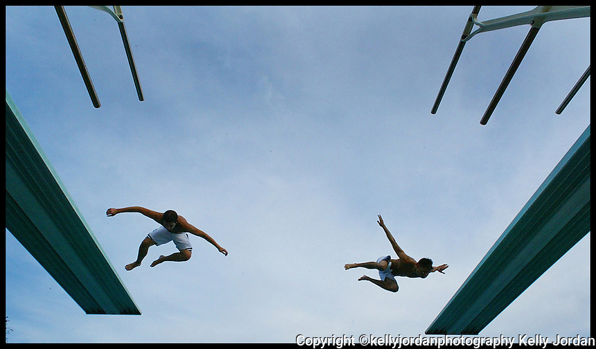 Kevin Mock, left, a Embry-Riddle Aeronautical University freshman from Pennsylvannia, and Jesse Florentine, a freshman from Pennsylvannia do a simultaneous dive of the high boards at the ERAU swimming pool.