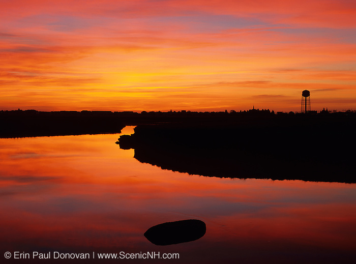 Sunrise over the salt marshes at Hampton Beach, New Hampshire on a cloudy day. The silhouette of a water tower can be seen on the right.