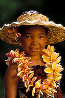 Young girl smiles with a plumeria lei.