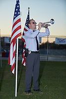Detective Cory Kluttz of the Kannapolis Police Department plays Taps at 5:15 PM as part of the Field of Honor tribute to veterans at Atrium Health Ballpark in Kannapolis, NC. There are 500 flags on display and a flag can be purchased to honor a veteran.  (Brian Westerholt/Four Seam Images)