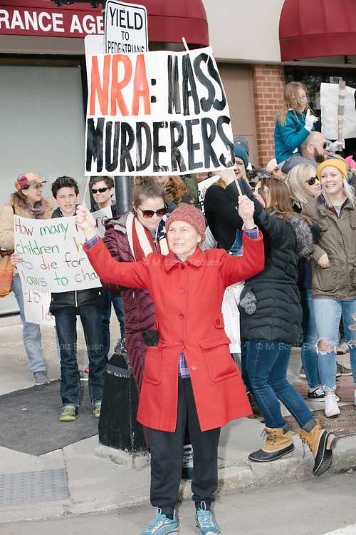 """People take part in the March For Our Lives protest, walking from Roxbury Crossing to Boston Common, in Boston, Massachusetts, USA, on Sat., March 24, 2018, in response to recent school gun violence. Here a woman holds a sign reading, on one side, """"NRA: Mass Murderers"""" and """"Repeal 2nd Amendment"""" on the other."""