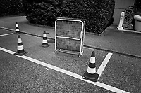Switzerland. Canton Ticino. Lugano. Four plastic traffic cones and a foldable bed are used by a moving company to reserve an empty parking space in the street.16.06.2020 © 2020 Didier Ruef