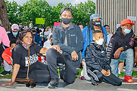 """People take a knee for 8 minutes and 46 seconds outside the Boston Police Department Headquarters during the """"Peaceful Children's March: Be the Change"""" demonstration in support of Black Lives Matter in Boston, Massachusetts, on Sun., June 7, 2020. The children's march was organized by siblings Naheem, 7, and Anaysha Benalfew, 10. The demonstration is part of a weeks-long nationwide response to the killing of George Floyd by Minneapolis police on May 25, 2020. The march started near the Nubian Square bus depot and continued to the nearby Boston Police Department headquarters, where marchers knelt for 8 minutes and 46 seconds, the time that police officers knelt on George Floyd's neck during his killing. A number of children, mostly people of color, then spoke about how people should be treated equally and how they wished they didn't have to grow up fearful that a police officer would kill them or their loved ones."""