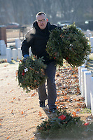 David Jetter of Springdale, a veteran of the U.S. Army, carries a load of wreaths Saturday, Jan. 9, 2021, while collecting the holiday wreaths with his family at the Fayetteville National Cemetery. The wreaths were placed in front of each grave in the cemetery in December by volunteers through the Wreaths Across America program and were collected by groups of volunteers organized by the Fayetteville National Cemetery Advisory Council who worked in shifts because of the pandemic. Visit nwaonline.com/210110Daily/ for today's photo gallery. <br /> (NWA Democrat-Gazette/Andy Shupe)