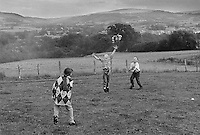 Kids playing in a meadow use a cuddly toy as a ball, at the Hay-on-Wye county fair.