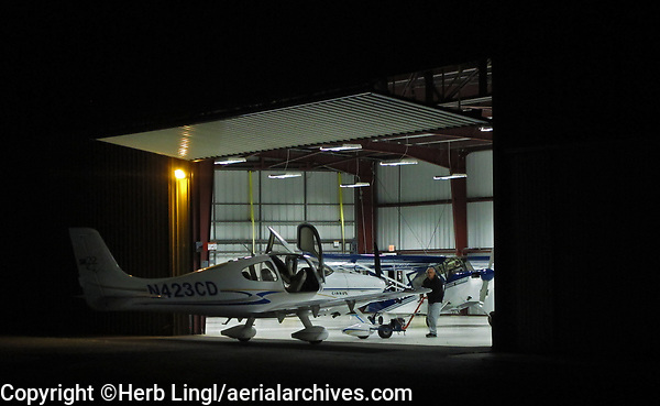 A Cirrus SR22 is towed out of Greg Goebel's hangar before dawn for an early morning flight, Petaluma Municipal Airport, Petaluma, Sonoma County, California