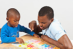 Boy, age 3, at home with father, playing with matching alphabet and illustration puzzle cards