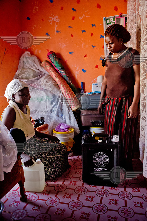 In the district of Kisalosalo, district of Kyebando, in the suburbs of Kampala, Mastulah Nakisozi (R) gives a neighbour water from a Solvatten solar water purifier. Nakisozi is part of a group of people infected with HIV who joined together to buy the purifier, with the help of an NGO, so they would have access to clean drinking water.