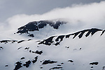 Dramatic mountain view of clouds and snow in Whittier, Alaska