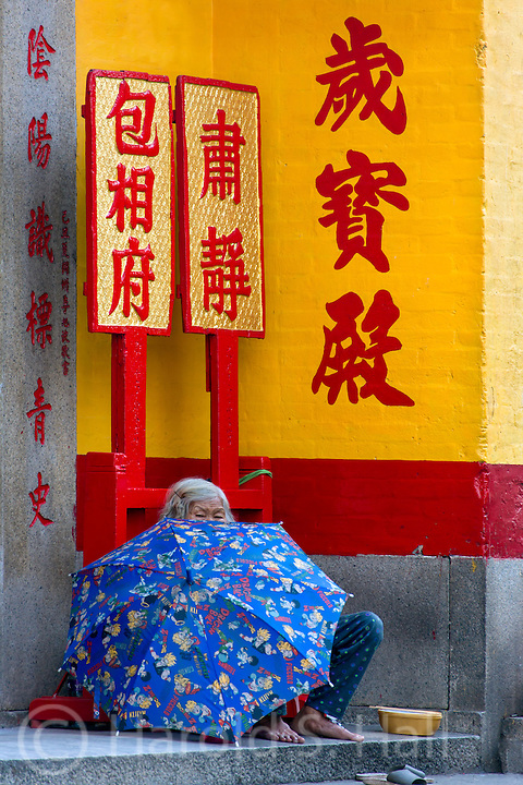 An elderly lady begs outside of a building in Macaw, China.