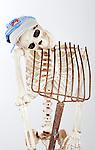 Skeleton with broken neck supported by pitchfork wearing cancer survivor's hat.
