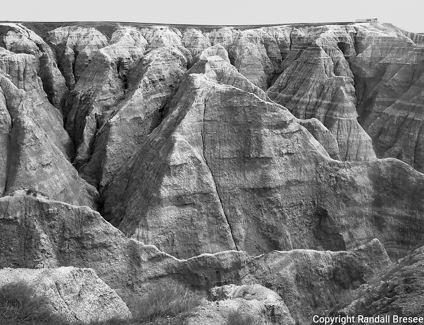 """""""Big Badlands Overlook"""" <br /> Badlands National Park, South Dakota<br /> <br /> The Badlands National Park includes spectacular layered rock and steep canyons formed by erosion. This photograph shows the Big Badlands Overlook. The overlook point has a bench for sitting which is enclosed in fencing and can be seen at the upper right of the photo. The bench and fence provide a sense of scale for the huge rock layers and steep canyons in this area."""