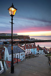 Great Britain, England, North Yorkshire, Whitby: Looking down steep steps at dusk over the Old Town and West Cliff
