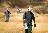 Orienteering classroom outdoors - male teenage students walking on grassy plain, holding orienteering maps. High School Students. Arizona.