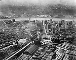 Pittsburgh PA:  Aerial view of Pittsburgh looking southwest over the Pennsylvania Railroad Station toward the Monongahela River, the South Side, and new Liberty Tunnels under construction.