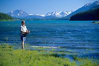 Man fishes along the sunny shore of Atlin Lake, Atlin, BC Canada