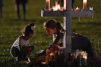 PARKLAND, FL - FEBRUARY 16: A young women places flowers at a memorial site that honors victims of the mass shooting at Marjory Stoneman Douglas High School, at Pine Trail Park on February 16, 2018 in Parkland, Florida. Police arrested 19-year-old former student Nikolas Cruz for killing 17 people at the high school.<br /> <br /> <br /> People:  Atmosphere
