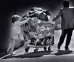 A young girl helps her mother with a shopping cart of possessions on a sidewalk in the tenderloin district of San Francisco, California.
