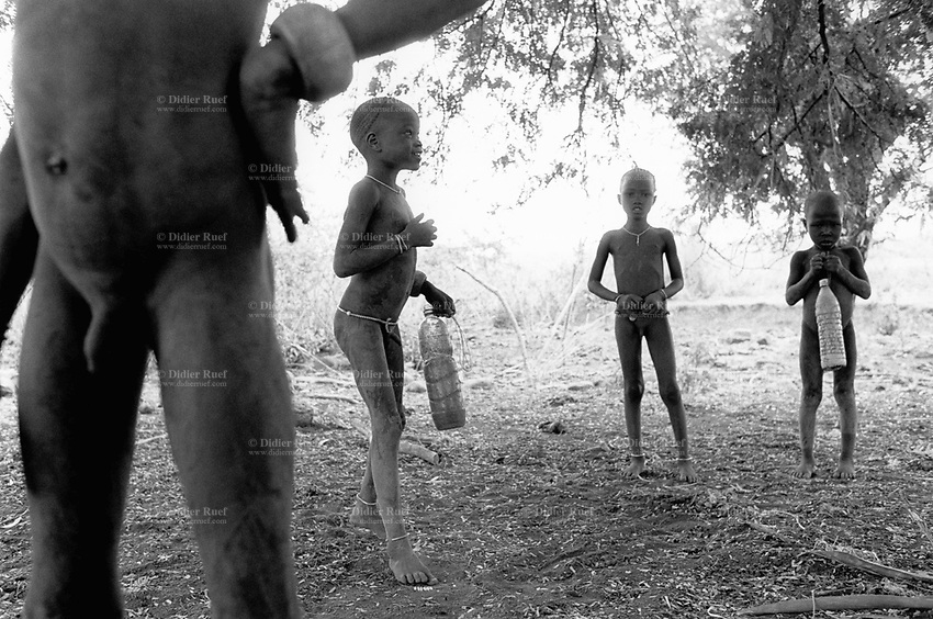 """Ethiopia. South Omo Zone. Salamago district. Muizo. Mursi tribe. Young boys with plastic bottles to hold drinkable water collected in river's bed. Agro-pastoralist group. Nomadic. Mursi women are known as """"disk-lip"""" women. The bottom lip is slit along its full length and the front bottom row of teeth are pulled out to accomodate the  ceramic disk  which is handmade with a rim around which the stretched lip is pulled. The disk is seen as a symbol of beauty and wealth, and often the younger girls will pierce and strech their ear-lobes, inserting a matching disk in the extended lobe. The Mursi tribe is located in the Debub Omo Zone (South Omo Zone) of the Southern Nations, Nationalities and Peoples's région. © 2001 Didier Ruef"""