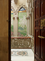 A door opens onto the main staircase, where stone arches frame views of a mosaic landscape
