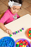 Education preschool 3-4 year olds girl sorting colored plastic bears into a pattern