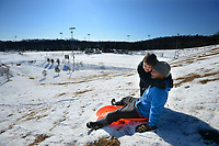 Austin Sutton (right) of Fayetteville gets a hug Saturday, Feb. 20, 2021, from his son, Titan Sutton, 8, while sledding near ball fields at Kessler Mountain Regional Park in Fayetteville. The Fayetteville City Council on Thursday approved a nearly $6.4 million construction contract to build a second four-field baseball complex at the park. Visit nwaonline.com/210221Daily/ for today's photo gallery. <br /> (NWA Democrat-Gazette/Andy Shupe)