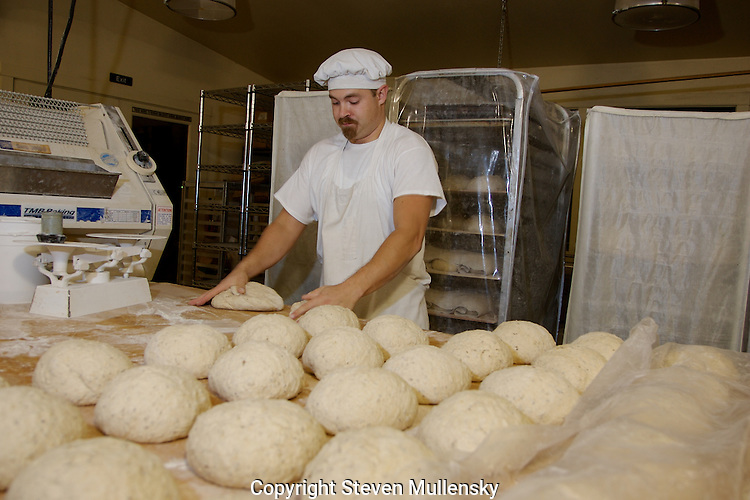 A baker kneads two balls of dough at once and turns them into loaves ready for the oven.