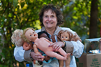 Susie Rasmussen holds four of the dolls she bought at an estate auction.<br /> <br /> The contents of a home on East Broadway went before the auction block Saturday. <br /> <br /> Eager bargain hunters took their time looking over prospective purchases hoping others didn't know of its true value or weren't interested in their item of choice.<br /> <br /> Many boxed items were sold with the buyer only interested in one item in the box of interest. Many buyers bought large lots of glass and pottery for a single knickknack in the collection.