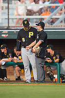 Home plate umpire Kaz Endo explains a call to Bristol Pirates manager Edgar Varela (6) during the game against the Johnson City Cardinals at Howard Johnson Field at Cardinal Park on July 6, 2015 in Johnson City, Tennessee.  The Pirates defeated the Cardinals 2-0 in game one of a double-header. (Brian Westerholt/Four Seam Images)