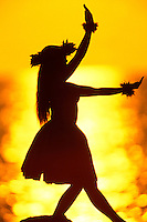 Young Hawaiian woman practicing her hula dancing at the beach at with a beautiful orange sunset