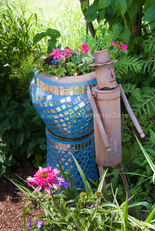 """Rusted iron """"tin man"""" ornament next to bright blue mirrored container garden pot of annual flowers geraniums, with ferns and echinacea in shaded spot"""