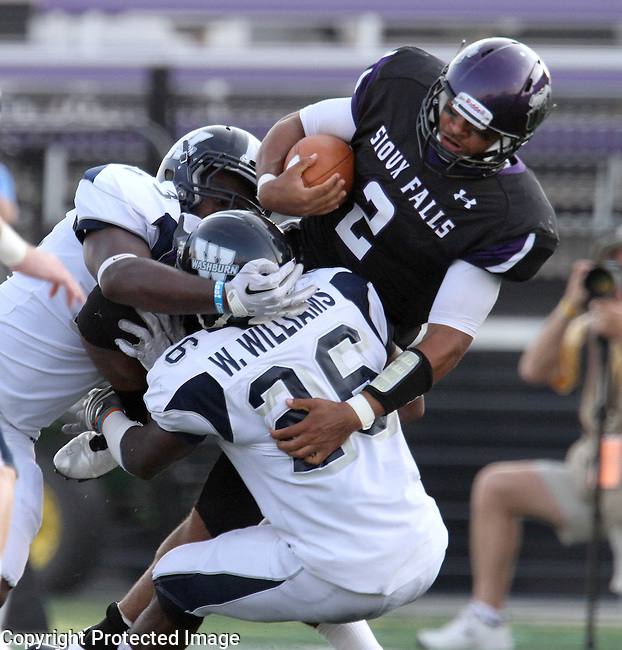 SIOUX FALLS, SD - SEPTEMBER 1: Carrington Hanna #2 of the University of Sioux Falls tries to squeeze out an extra yard past a pair of defenders including Willie Williams #26 from Washburn University in the first quarter of their game Thursday night at Bob Young Field in Sioux Falls.  (Photo by Dave Eggen/Inertia)