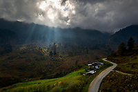 Sunlight burst through heavy rain clouds illuminating the forested Himalayan foothills. The ascent to Pele-La Pass from Kgebji village (Tashi choeling restaurant) in Longte Valley, Bhutan
