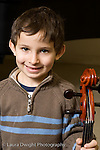 Elementary School New York male kindergarten student arts enrichment music boy posing with cello vertical