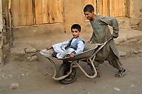 Boy in wheelbarrow.