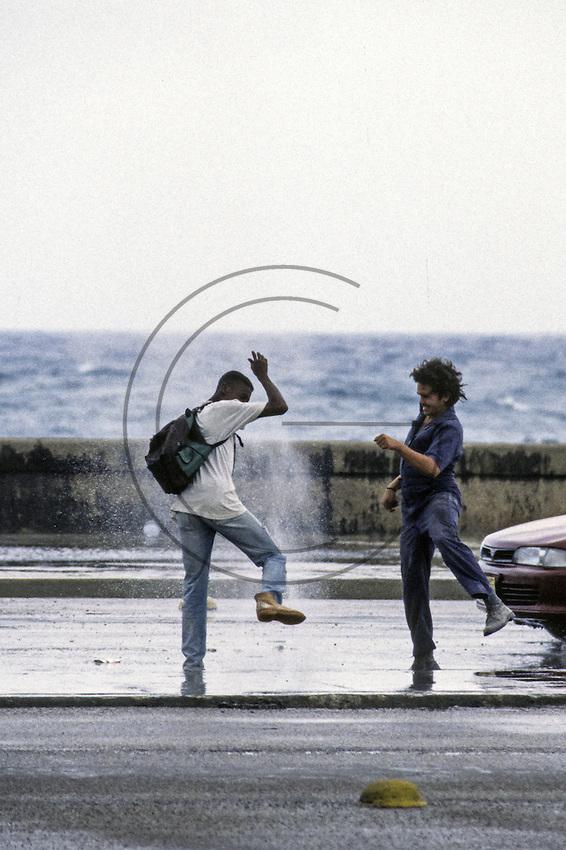 boys play avoiding spryed water from the manhole in the Malecón in Havana Cuba