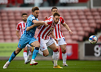21st April 2021; Bet365 Stadium, Stoke, Staffordshire, England; English Football League Championship Football, Stoke City versus Coventry; Rhys Norringrton-Davies of Stoke City and Matt Godden of Coventry City chases a loose ball