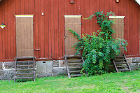 A farm building with three doors. Nas. Vimmerby town Smaland region. Sweden, Europe.
