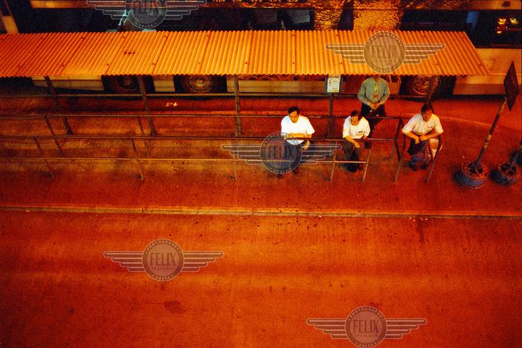 Men wait at a bus stop.