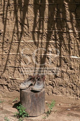 Para State, Brazil. Worn out pair of boots on a block of tree trunk in front of an adobe daub wall with shadows from the thatch.
